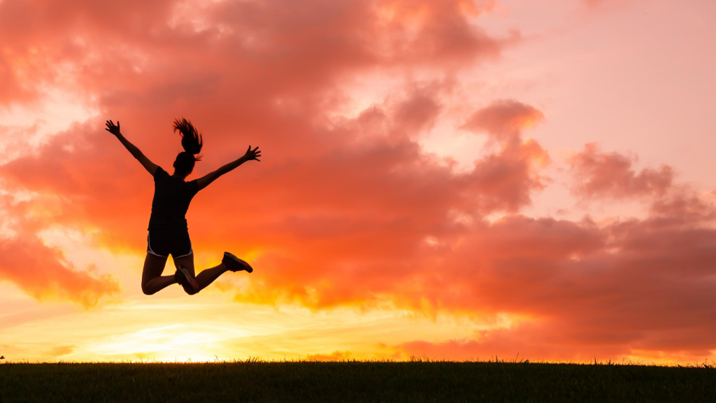 Photo of girl in workout clothes jumping in front of a sunset