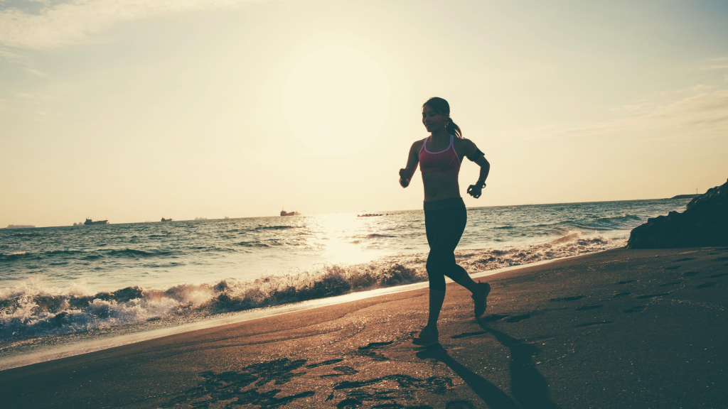 Photo of young woman running on the beach.